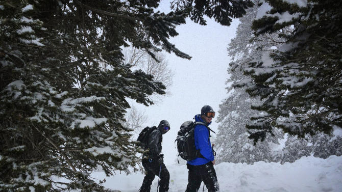 In this photo taken Friday, Feb. 22, 2013, Associated Press writer Sebastian Abbot, right, and Kashmiri mountain guide Javed Reshi stand in the trees during snowfall in Gulmarg, Kashmir.  Gulmarg, a ski resort nestled in the Himalayan mountains in Indian-held Kashmir is one of the most militarized places on earth. (AP Photo/Kevin Frayer)