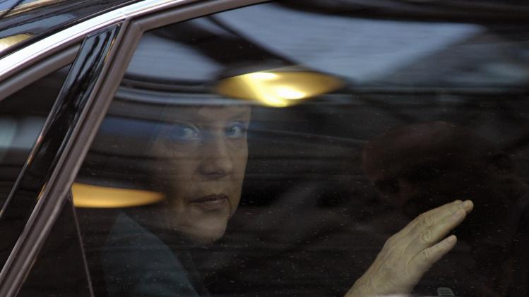 Germany's Chancellor Merkel looks out from her car upon arriving at a European Union leaders summit at the EU council headquarters in Brussels