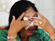 Cambodian woman Lay Bony, who lost 11 relatives including her husband and children under the hardline Khmer Rouge communist regime, is seen crying during an interview at her house in Phnom Penh, on March 7, 2012
