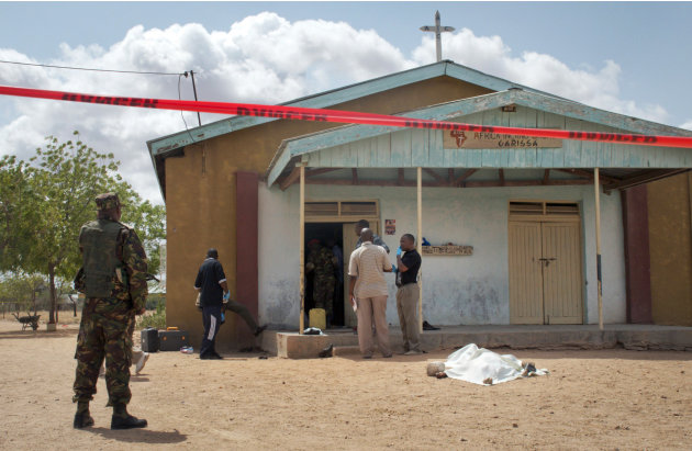 Members of the Kenyan security forces inspect the scene, as a body lies covered by a sheet, outside the African Inland Church in Garissa, Kenya Sunday, July 1, 2012. Gunmen killed two policemen guardi