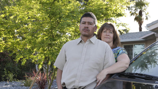 In this photo taken Monday, March 24, 2014, Martin Del Agua and his wife, Julie are seen at their home in Sacramento, Calif. Martin Del Agua faced deportation when he was arrested after a neighbor complained that he was playing music to loud in his garage.(AP Photo/Rich Pedroncelli)