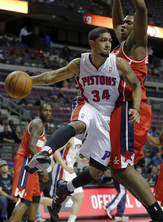 Detroit Pistons guard Peyton Siva (34) passes the ball against Washington Wizards forward Kevin Seraphin during the second half of a preseason NBA basketball game Tuesday, Oct. 22, 2013, in Auburn Hil