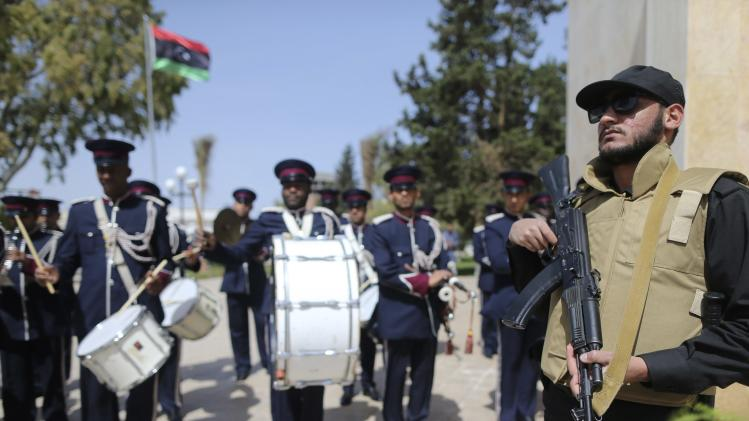A security officer stands near military band in front of hall hosting first meeting of members of constituent body to draft Libyan constitution, in Al-Bayda