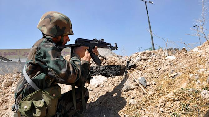 In this photo released on June 5, 2013 by the Syrian official news agency SANA, a Syrian soldier loyal to President Bashar Assad aims his weapon near the Homs-Damascus highway, central Syria. Syrian troops and their Lebanese Hezbollah allies captured a strategic border town Wednesday after a grueling three-week battle, dealing a severe blow to rebels and opening the door for President Bashar Assad's regime to seize back the country's central heartland. The regime triumph in Qusair, which Assad's forces had bombarded for months without success, demonstrates the potentially game-changing role of Hezbollah in Syria's civil war. (AP Photo/SANA)