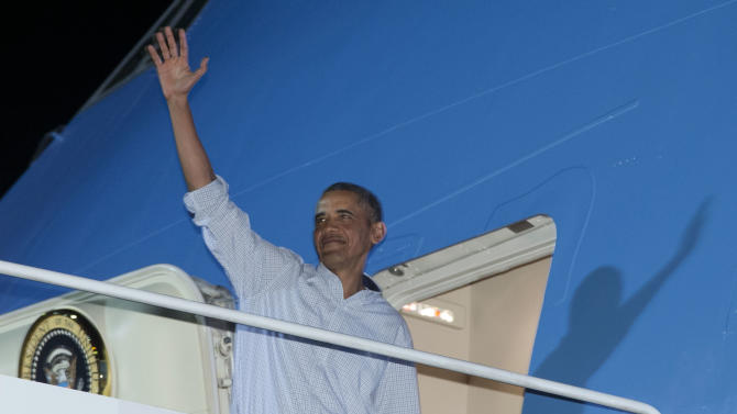 President Barack Obama waves as he boards Air Force One at Honolulu Joint Base Pearl Harbor-Hickam, in Honolulu, Saturday, Jan. 4, 2014, as they travel back to Washington after their annual family vacation. (AP Photo/Carolyn Kaster)