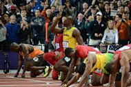 Jamaica&#39;s Usain Bolt (C) looks up prior to taking the start of the men&#39;s 100m final at the athletics event during the London 2012 Olympic Games in London