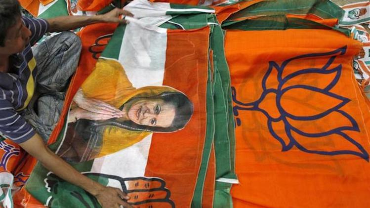 A worker looks at a Congress party flag carrying a picture of its party chief Sonia Gandhi next to flags of India's main opposition Hindu nationalist Bharatiya Janata Party (BJP) inside an election campaigning material workshop ahead of the state assembly elections on the outskirts of Ahmedabad October 10, 2012. REUTERS/Amit Dave/Files