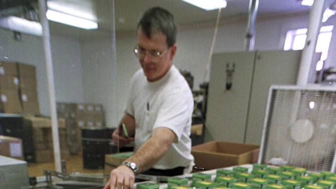 FILE - In this Jan. 28, 1999 file photo, Al Adams works on the production line at the Bag Balm plant in Lyndonville, Vt. The 115-year-old family business was sold in September 2014 to a group of investors who are promising to expand the brand, but not change the formula. Bag Balm began as a staple for dairy farmers treating the inflamed udders of cows, but over the generations, the salve has been used for everything from sunburns to the paws of dogs searching the World Trade Center's rubble after 9/11. (AP Photo/Toby Talbot, File)