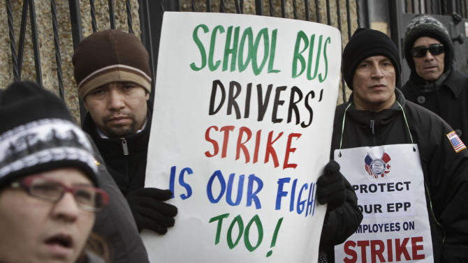 FILE- In this Jan. 17, 2013 file photo, striking school bus drivers walk a picket line outside the Atlantic Express school bus facility in the Queens borough of New York.  Leaders of school bus drivers' union, Local 1181 of the Amalgamated Transit Union, are ending their month long strike in New York City, Friday, Feb. 15, 2013. The strike was suspended a day after five Democratic mayoral candidates sent a letter to the union asking drivers to return to work, promising that if elected, they will revisit the job security issue fueling the strike.  (AP Photo/Bebeto Matthews, File)