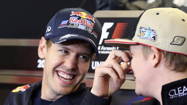 Red Bull driver Sebastian Vettel, left, of Germany, smiles as he talks with Lotus driver Kimi Raikkonen, of Finland, during a news conference at the Circuit of the Americas race track Thursday, Nov. 15, 2012, in Austin, Texas. Formula One's U.S. Grand Prix auto race is scheduled for Sunday at the track. (AP Photo/Luca Bruno)