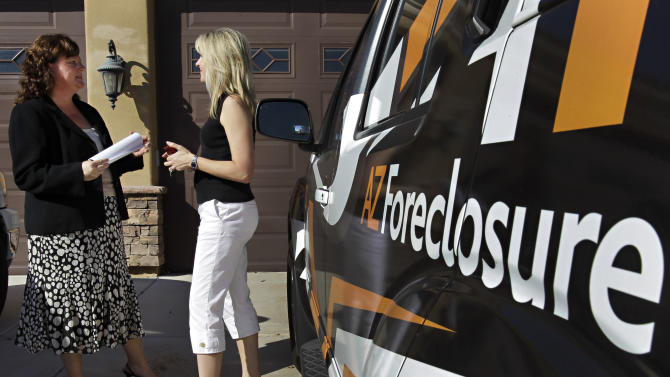 In this Oct. 13, 2010 photo, realtor Teresa Sciubba, left, talks with real estate investor Kristin Gragg outside a foreclosed property, in Chandler, Ariz. (AP Photo/Matt York)