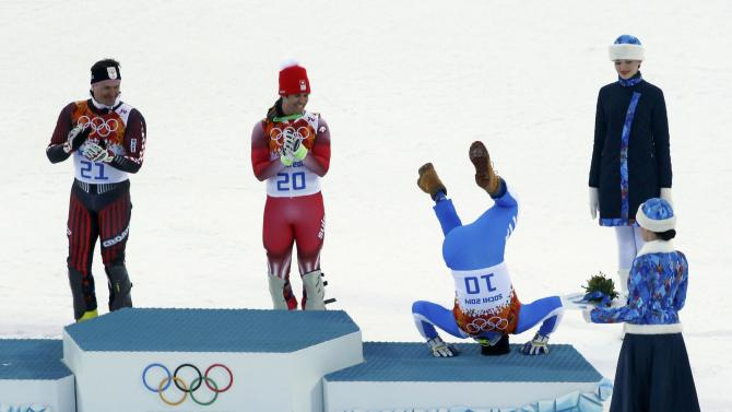 Third-placed Innerhofer does a somersault after the men's alpine skiing super combined event at the Sochi 2014 Winter Olympics