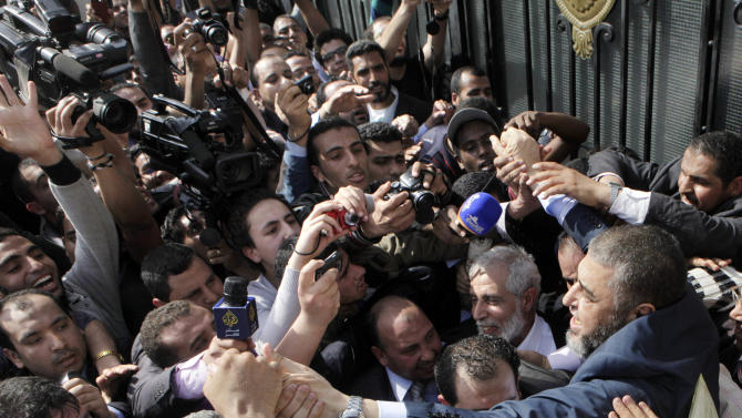 Muslim Brotherhood presidential hopeful Khairat el-Shater, right, is surrounded by hundreds of supporters and cameramen after he submitted his candidacy papers at the Higher Presidential Elections Commission, in Cairo, Egypt, Thursday, April 5, 2012. (AP Photo/Amr Nabil)