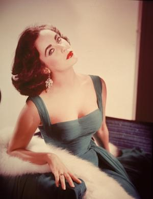 Elizabeth Taylor in a form-fitting green dress as she sits with her head tilted back exposing her neck, circa 1950s -- Getty Images