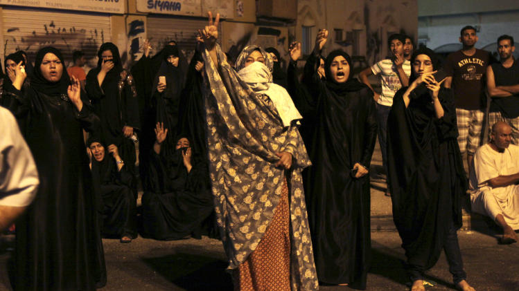 "Bahraini villagers shout anti-government slogans toward riot police who were cordoning off the nearby site where a youth was killed, allegedly by police shotgun fire,  in Sadad, Bahrain, early Saturday, Sept. 29, 2012. An Interior Ministry statement said a police patrol was attacked with petrol bombs and iron rods, and one person died when ""policemen defended themselves."" A witness among protesters said demonstrators were marching against the government when a policeman suddenly stepped out near the youth and shot him at close range. (AP Photo/Hasan Jamali)"