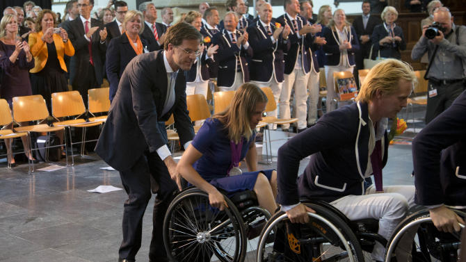 Prime Minister Mark Rutte, left, pushes London 2012 Paralympic silver medallist wheelchair racer Amy Siemons up the ramp during a celebration honouring medal-winning Dutch Paralympic athletes on the eve of parliamentary elections in The Hague, Netherlands, Tuesday Sept. 11, 2012. According to a summary of recent polls compiled by national broadcaster NOS Tuesday, Rutte's free-market VVD party is running neck-and-neck with the center-left Labor Party PvdA of Diedrik Samsom. (AP Photo/Peter Dejong)