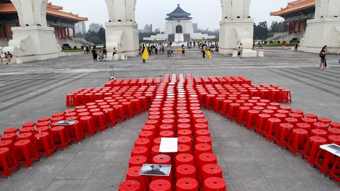 "Hundreds of red plastic chairs are arranged to form one of Chinese characters of Chinese artist and activist Ai Weiwei's name to support him on the Liberty Square in front of the Chiang Kai-shek Memorial Hall in Taipei, Taiwan, Saturday, June 4, 2011. Chinese police detained Ai on April 3, 2011 without laying any official charges and the authorities alleged a company controlled by Ai evaded ""huge amount"" of tax. (AP Photo/Chiang Ying-ying)"