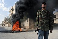 A Syrian rebel stands next to burning tyres set on fire in order for the smoke to obscure the vision of regime pilots in the northwestern town of Maaret al-Numan on October 20. Syrian warplanes raided the rebel-held town of Maaret al-Numan on Wednesday, monitors said, as peace envoy Lakhdar Brahimi prepared to brief the UN Security Council on his ceasefire efforts