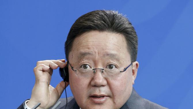 Mongolian President Elbegdorj adjust his earphones addresses a news conference at the Chancellery in Berlin