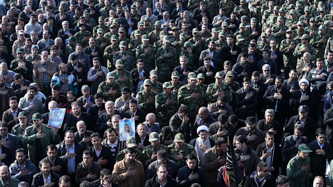 "Iranian civilians and armed forces members attend the funeral ceremony of Brig. Gen. Hamid Taqavi, a senior Revolutionary Guard commander who was killed during a battle against the Islamic State extremist group in Iraq, outside the Guard compound in Tehran, Iran, Monday, Dec. 29, 2014. The Guard said Sunday that Taqavi was ""martyred while performing his advisory mission"" in Samarra, a town north of Baghdad that is home to a major Shiite shrine. He is the highest ranking Iranian officer known to have been killed abroad since the Iran-Iraq war in the 1980s, in which he fought. (AP Photo/Ebrahim Noroozi)"