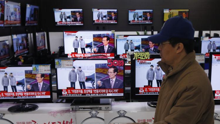 A man walks past televisions showing reports on the execution of Jang Song Thaek, in Seoul