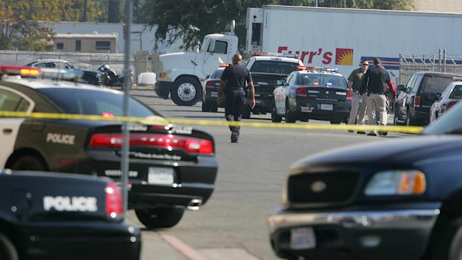 Police search an area where a workplace shooting occurred that killed one person and wounded several others at Valley Protein, formally known as Apple Valley Farms Tuesday, Nov. 6, 2012, in Fresno, Calif.  Police say a parolee who worked at the  Fresno chicken processing plant opened fire at the business on Tuesday, killing one person and wounding three others, before shooting himself. Police Chief Jerry Dyer said they didn't know what prompted the attack by 42-year-old Lawrence Jones midway through his shift at Apple Valley Farms. Other workers told police he did not appear to be himself when he arrived at the plant for work. (AP Photo/Gary Kazanjian)