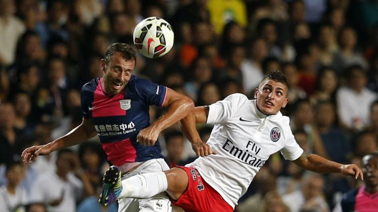 Paris Saint-Germain's Marco Verratti and Dani Cancela of local team Kitchee leap for ball during friendly match in Hong Kong