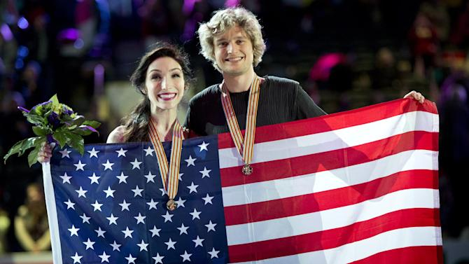 Gold medallists Meryl Davis,left, and Charlie White, of the United States, pose with their medals and an American flag during the flower ceremony in the ice dancing competition at the World Figure Skating Championships in London, Ontario, Saturday March 16, 2013. (AP Photo/The Canadian Press, Paul Chiasson)