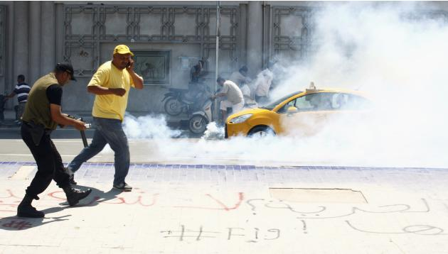 Police fire tear gas to break up a protest, near the parliament building in Tunis