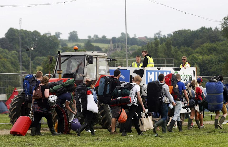 Festival goers arrive at the Glastonbury Music Festival site on Wednesday, June 26, 2013. Thousands are to arrive for the three day festival that starts on Friday, June 28 2013 with headliners, Arctic Monkeys, the Rolling Stones and Mumford and Sons. (Photo by Jim Ross/Invision/AP)