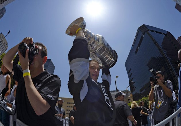 Los Angeles Kings right wing Dustin Brown,center, holds up the Stanley Cup trophy while riding in a parade, Monday, June 16, 2014, in Los Angeles. The...