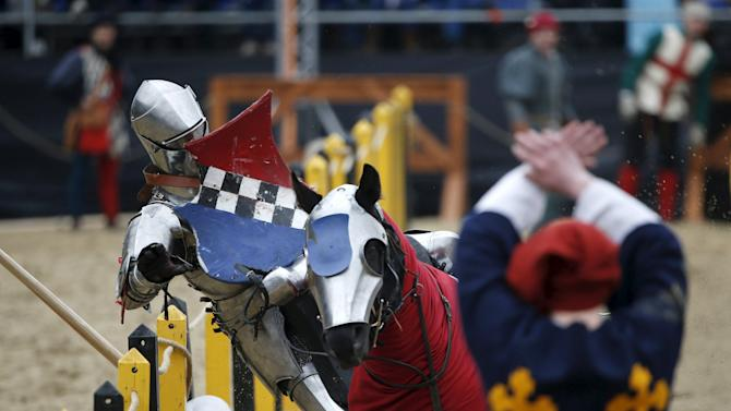 A participant falls down from a horse as he competes during the Saint George international knight tournament in Moscow