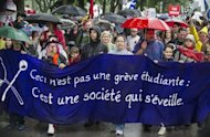 Thousands of people took to the streets of Montreal braving driving rain to protest planned tuition hikes after talks between students and the Quebec government broke down. Banner reads &quot;This is not a student strike, it&#39;s a community awakening&quot;