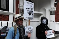 "A man holds a ""Free Assange - No Extradition"" sign alongside a protester wearing a Guy Fawkes mask as they demonstrate outside the Ecuadorian embassy in London, on June 23. Ecuador's foreign minister has said that rape and sexual assault cases lodged in Sweden against Julian Assange are laughable, but no ruling has yet been made on the WikiLeaks founder's asylum application"