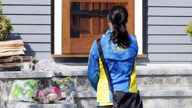 Runner Megan Cloke pauses after placing flowers on the doorstep of the Richard house in the Dorchester neighborhood of Boston,Tuesday, April 16, 2013. Martin Richard,8, was killed in Mondays' bombings at the finish line of the Boston Marathon. The boy's mother, Denise, and 6-year-old sister, Jane, were badly injured.  (AP Photo/Michael Dwyer)