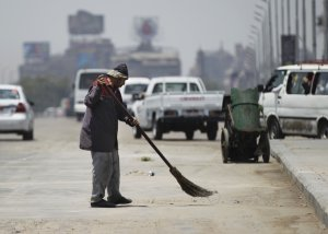 A man sweeps on a bridge leading to Tahrir Square in …