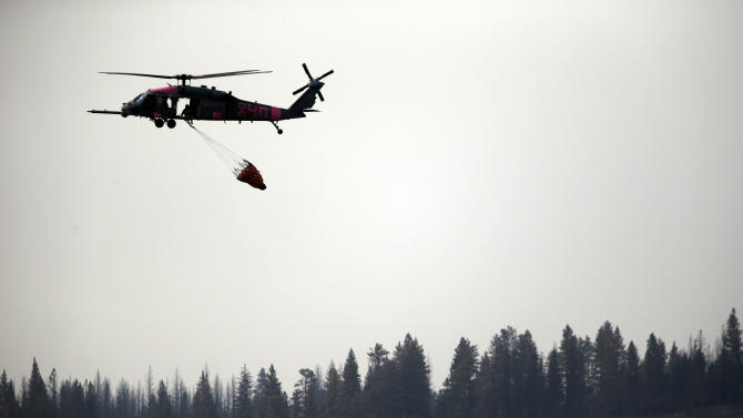 Fire crews prepare to drop water unto the Ponderosa Fire from a helicopter near Mineral, Calif., Thursday, Aug.  23, 2012. The Ponderosa Fire was 57 percent contained, with full containment expected early next week. The blaze threatened 900 other homes Thursday as it burned a new front to the south. More than 2,500 firefighters are battling the wildfire, which grew to 44 square miles in the hills about 25 miles southeast of Redding. (AP Photo/Marcio Jose Sanchez)