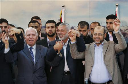 Senior Fatah official Azzam Al-Ahmed, head of the Hamas government Ismail Haniyeh and senior Hamas leader Moussa Abu Marzouq hold their hands after announcing a reconciliation agreement in Gaza City