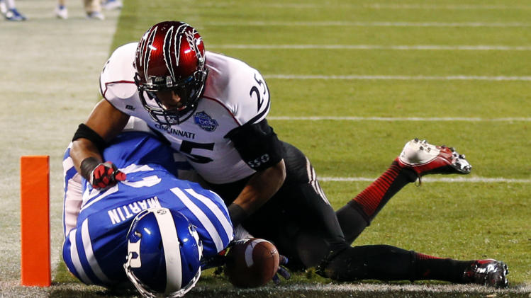 Duke's Ross Martin (35) fumbles the ball short of the end zone as Cincinnati's Arryn Chenault (25) defends during the first half of the Belk Bowl NCAA college football game in Charlotte, N.C., Thursday, Dec. 27, 2012. (AP Photo/Chuck Burton)