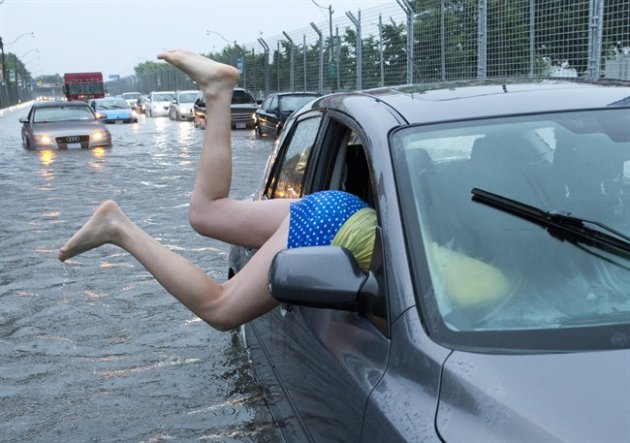 A woman gets back into her flooded car on the Toronto Indy course on Lakeshore Boulevard in Toronto on Monday, July 8 2013. THE CANADIAN PRESS