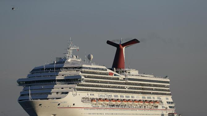 FILE - In this Feb. 14, 2013 file photo the cruise ship Carnival Triumph is towed into Mobile Bay near Dauphin Island, Ala., Thursday, Feb. 14, 2013. Want to know about a ship's track record for being clean? Want to assess how good or sanitary the food is? It's not that easy to find, in part because there's no one entity or country that oversees or regulates the industry with its fleet of ships that are like mini cities floating at sea. In the case of Carnival Cruise Lines, the owner of the Carnival Triumph that spent days in the Gulf of Mexico disabled after an engine fire, vacationers looking up information about the ship before boarding would have found mostly clean marks and few red flags. (AP Photo/Dave Martin)