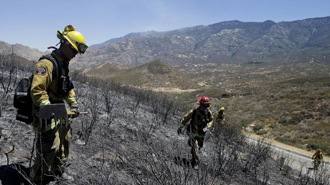 Firefighters look for hot spots as they walk through the scorched area on Friday, Aug. 9, 2013, near Banning, Calif. Southern California firefighters are facing another day of battle as they try to corral a wildfire that has destroyed 26 homes. (AP Photo/Jae C. Hong)