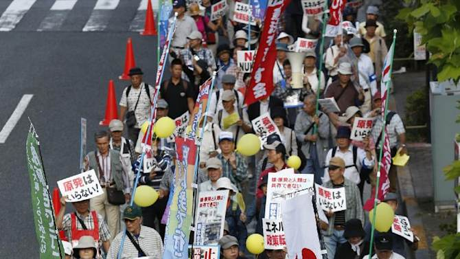 Anti-nuclear protesters hold placards while marching during a Sayonara (good-bye) Nukes anti-nuclear power protest rally in Tokyo, Tuesday, Sept. 23, 2014. (AP Photo/Shizuo Kambayashi)