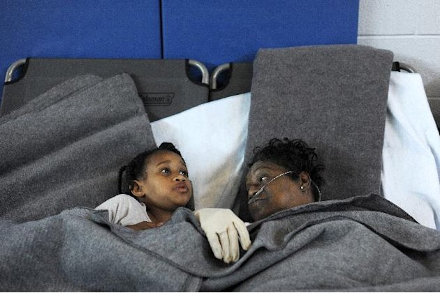 Marcia McCloud (right) and her great-granddaughter Makayla Milton, find some comfort together at the Red Cross cooling shelter at Sandusky Middle School in Lynchburg, Va., July 1, 2012. Milton was vis