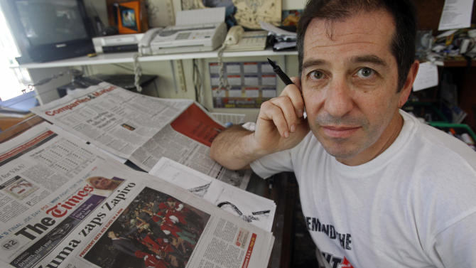 In this photo taken Tuesday, Dec. 14, 2010 cartoonist Jonathan Shapiro, who signs his work as 'Zapiro',  poses for a photo next to a local news paper at his office, in Cape Town, South Africa. South African president Jacob Zuma, told foreign correspondents on Monday, Oct. 29, 2012 that the freedom of expression needs to be balanced to the right to dignity and privacy to all South Africans after he agreed to withdraw a defamation case against Zapiro  who depicted him poised to rape Lady Justice. (AP Photo/Schalk van Zuydam-file)