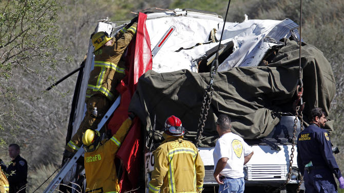 San Bernardino County firefighters hang a drape over the smashed front of a tour bus where at least eight people were killed and 38 people were injured after it collided with tow other vehicles just north of Yucaipa, Calif., Sunday, Feb. 3, 2013. The bus was carying a group from Tijuana, Mexico. (AP Photo/Reed Saxon)