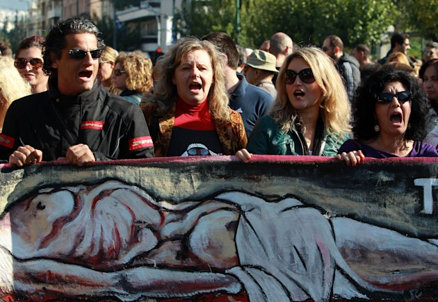 Protesting civil servants carrying a banner showing an image of an emaciated body shout slogans during a  rally outside the Public Sector Reform ministry in Athens on Tuesday, Nov. 13, 2012. Civil servants face a new round of pay cuts under austerity measures approved by parliament last week. Despite concerns over Greece&#39;s long-term economic outlook, the country&#39;s euro partners and the International Monetary Fund are expected to agree on the release of the next tranche of the bailout over the next week. (AP Photo/Thanassis Stavrakis)