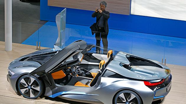 A member of the media takes snapshots of the BMW i8 concept car, on the eve of the opening of the Paris Auto Show.