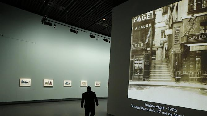 "A man walks by a Eugene Atget photography display as part of the retrospective for Edward Hopper, one of the great American 20th century artists at Paris' Grand Palais Museum, in Paris, Monday, Oct. 8, 2012.  This major Hopper retrospective reveals that the 20th century painter known for his rendering of American life, also drew inspiration from France, and includes some 128 Hopper works, such as the masterpieces ""Nighthawks"" and ""Soir Bleu"".(AP Photo/Francois Mori)"