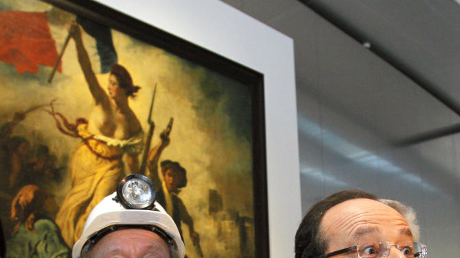 "France's President Francois Hollande, right, is seen with a former miner, Lucien Laurent in front of "" La Liberte Guidant le Peuple"", a painting by Eugene Delacroix during the inauguration of the Louvre Museum in Lens, northern France, Tuesday, Dec. 4, 2012.  The museum in Lens is to open on Dec. 12, as part of a strategy to spread art beyond the traditional bastions of culture in Paris to new audiences in the provinces. (AP Photo/Michel Spingler, Pool)"